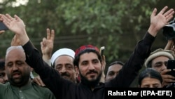FILE: The leader of Pakistan's Pashtun Tahafuz (Protection) Movement (PTM) Manzoor Pashteen (c) waves to supporters during a demonstration in Lahore in April.