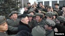 Солтүстік Корея басшысы Ким Чен Ын мен ғалымдар Unha-3 спутнигінің ғарышқа ұшқанына қуанып тұр. 13 желтоқсан 2012 жыл.