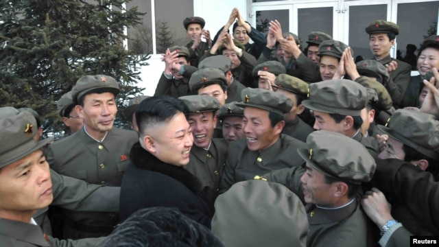 Kim Jong Un (center) celebrates with scientists and technicians after the launch of a rocket in mid-December.