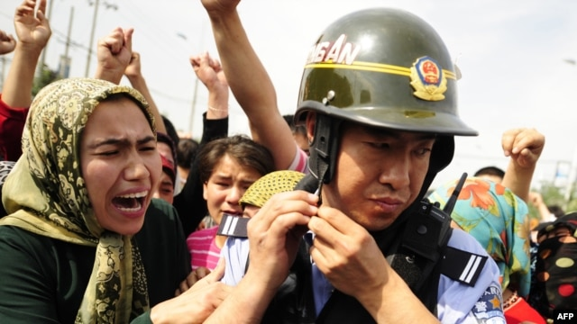 Uyghur women surround a Chinese riot policemen as they protest in Urumqi on July 7.