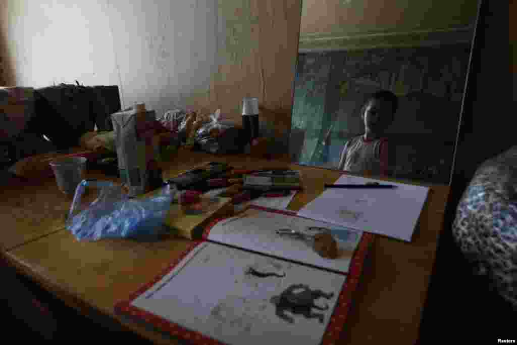 A child from a family who has fled from fighting in Slovyansk is seen in a mirror at temporary accommodation in a dormitory in the town of Ilovaysk on June 3.