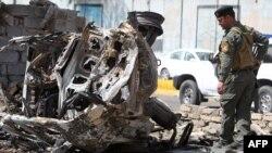 رجل أمن عراقي يتفحّص آثار تفجير في بغداد