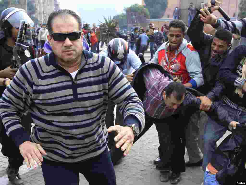 A plainclothes policeman confronts a foreign journalist during a demonstration in Cairo on January 28.