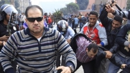 Egypt -- A plainclothes policeman (L) runs to attack a foreign journalist during a demonstration in Cairo, 28 January, 2011