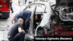გამომძიებლები ამოწმებენ აფეთქებულ მანქანას, რომელშიც დაიღუპა პაველ შერემეტი. კიევი, 2016 წ. 20 ივლისი.