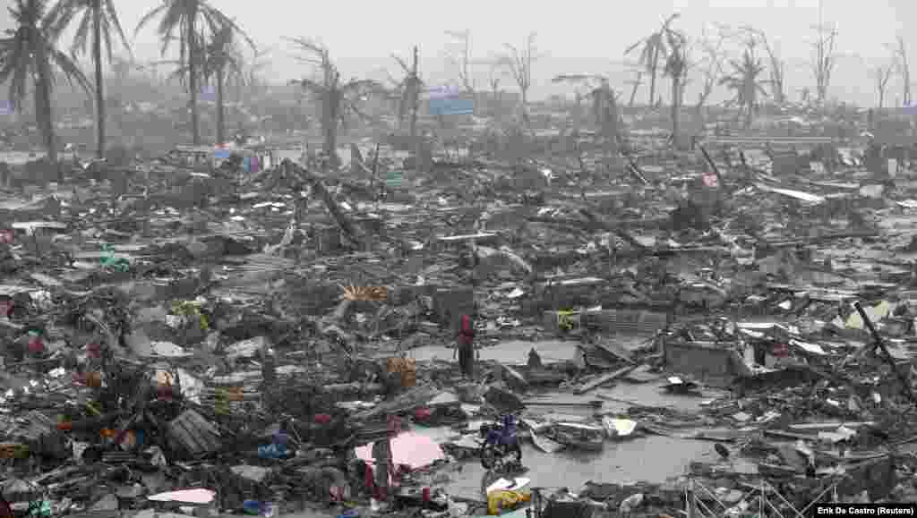 Survivors stand among the ruins of houses after Typhoon Haiyan battered the city of Tacloban in the Philippines on November 10. As many as 10,000 people died as a result of the typhoon, and an estimated 660,000 Filipinos were displaced.