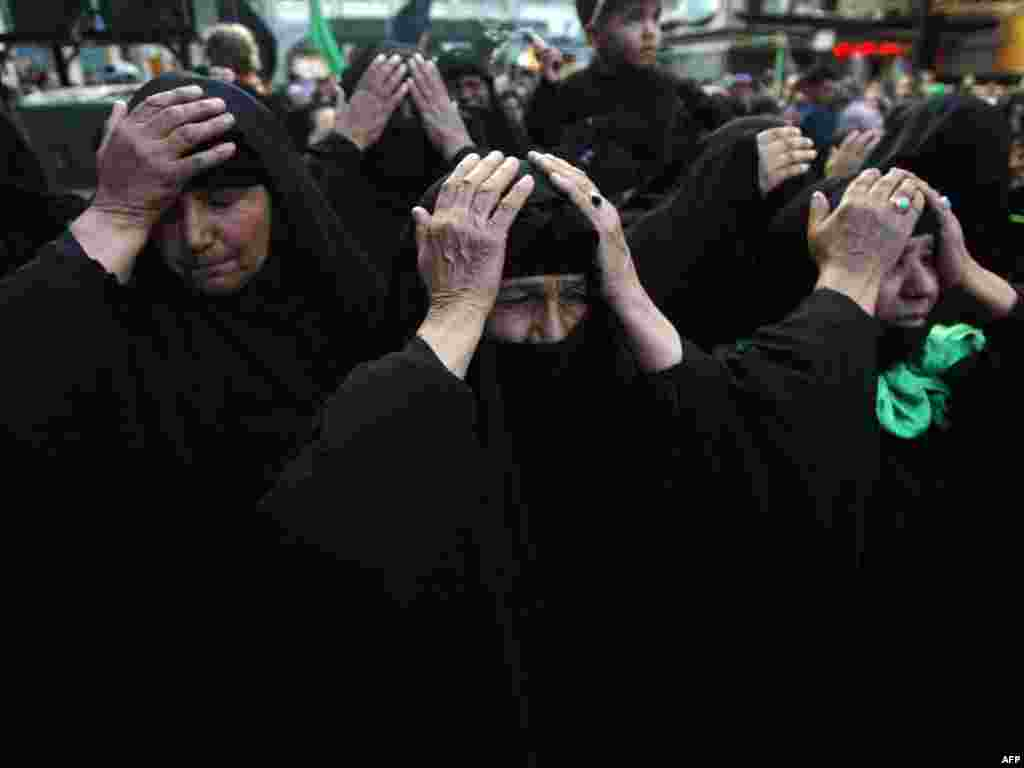 Iraq -- Muslim Shiite women beat their heads in the courtyard of the Imam Abbas Shrine in the southern holy city of Karbala on 02Feb2010 - IRAQ, Karbala : Muslim Shiite women beat their heads in the courtyard of the Imam Abbas Shrine in the southern holy city of Karbala, 110 kms (70 miles) south of the Iraqi capital Baghdad, as they take part in the Shiite mourning day of Arbaeen, on February 2, 2010. The Arbaeen religious event marks the end of 40 days of mourning after the Ashura anniversary that commemorates the seventh century killing of the grandson of Prophet Mohammed, the revered Imam Hussein. Arbaeen will see tens of thousands of Iranian pilgrims pass through Baghdad en route to Karbala to pay homage at the Imam Hussein shrine. AFP PHOTO/MOHAMMED SAWAF POTW05