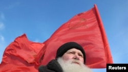 A demonstrator with a red Soviet flag attends a protest rally in Barnaul.