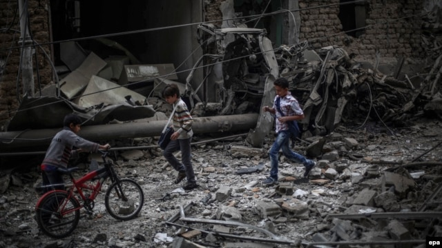 Syrian boys run past a destroyed field hospital in the rebel-held area of Douma, on the outskirts of Damascus, on October 29.