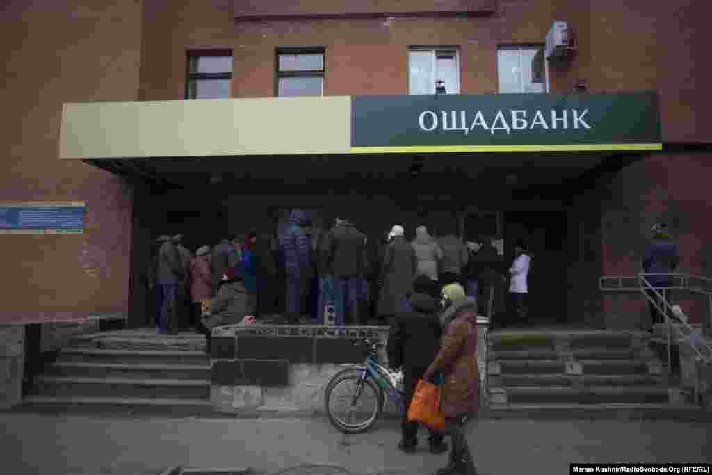 Зі сторони під контролем угруповання «ЛНР» на контрольовану Україною територію люди прямують за пенсіями та дешевшими продуктами. На фото – черга до банкомату «Сбербанку» у центрі Станиці Луганської. За словами місцевої жительки, зранку тут збирається черга до тисячі людей