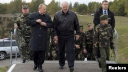 Russian President Vladimir Putin (left, front) and Belarusian counterpart Aleksandr Lukashenka (center, front), with Lukashenka's son alongside them, visit the joint war games Zapad-2013 at the Gozhsky firing range in Grodno on September 26.