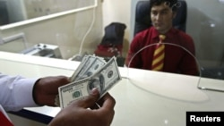 A customer counts his money after making a withdrawal at Azizi Bank's main branch in Kabul. (file photo)