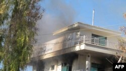 Smoke rises at a branch of the Kabul Bank where Taliban militants detonated a suicide bomb in Lashkar Gah, capital city of Helmand province on December 17.