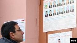 Молодой человек смотрит на фотографии кандидатов в депутаты парламента. Душанбе, 27 февраля 2015 года.