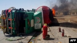 Bystanders inspect the site of a traffic accident in on the main Kabul-Kandahar Highway, May 8.