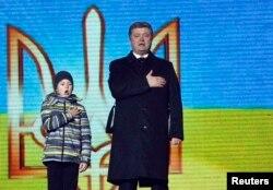 Президент Украины Петр Порошенко и сын одного из погибших Владислав Цыпун на памятной церемонии в первую годовщину трагедии