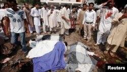 Жарылыстан қаза болғандардың мәйіттері жанында жиналып тұрған пәкістандық христиандар. Пешавар, 22 қыркүйек 2013 жыл