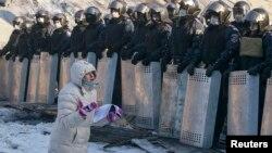 Женщина стоит на коленях перед милиционерами. Киев, 24 января 2014 года.