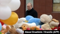 Russian President Vladimir Putin lays flowers in tribute to the victims of a fire at a shopping center in Kemerovo, a disaster that appears to have dented his poularity.