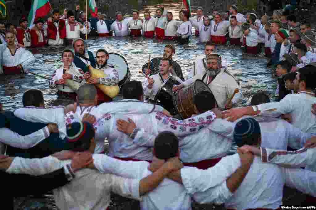 Bulgarian men perform the traditional horo dance in the icy waters of the Tundzha River in the town of Kalofer, as part of Epiphany Day celebrations on January 6. As a tradition, an Eastern Orthodox priest throws a cross into the river and it is believed that the one who retrieves it will be healthy throughout the year. (AFP/Nikolai Doychinov)