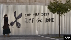 """Жительница Афин на фоне графити с призывом: """"МВФ, убирайся домой"""", 20 февраля 2015"""