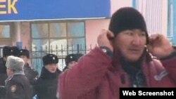 """Человек в рабочей спецовке, рядом стоят полицейские. Жанаозен, 16 декабря 2011 года. Скриншот с видеопортала """"Стан.кз""""."""