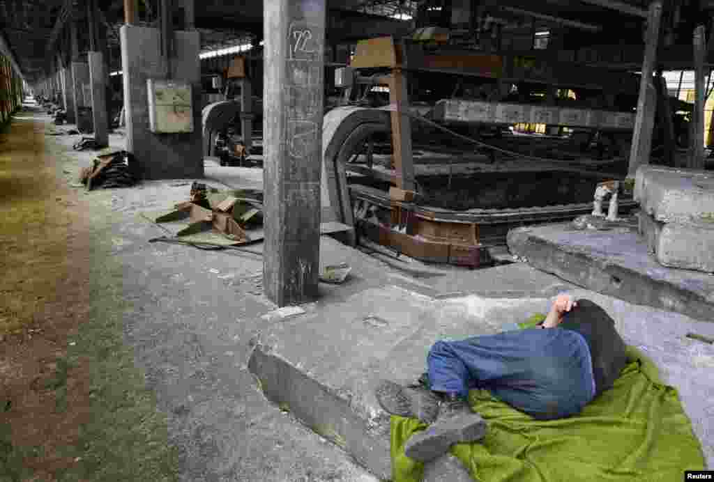 An employee takes a nap in a shutdown electrolysis plant in Montenegro's Podgorica Aluminum Plant. (Reuters/Stevo Vasiljevic)