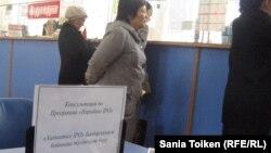 """Табличка """"Консультация по программе """"Народное IPO"""" на столе, за которым нет консультанта, в здании Главпочтамта. Актобе, 6 ноября 2012 года."""