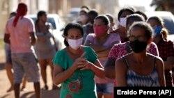Люди в масках на окраине бразильской столицы. 2 августа 2020 года.