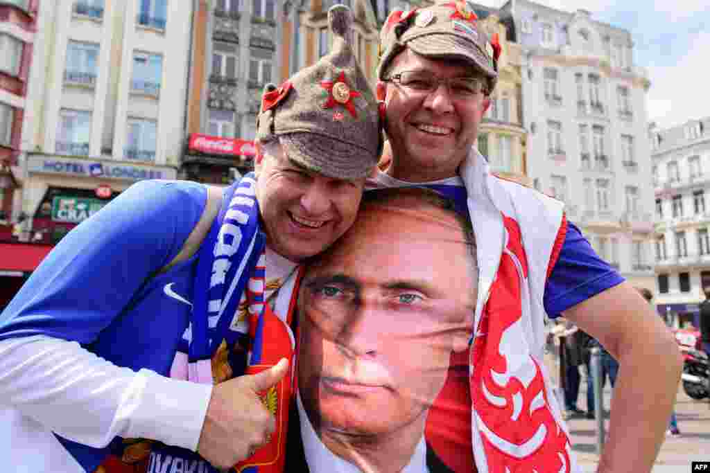 A Russian soccer fan poses with a fellow fan wearing a T-shirt featuring Russian President Vladimir Putin as they walk in central Lille, France, ahead of the match between Russia and Slovakia in the Euro 2016 championship. Russia lost 2-1. (AFP/Leon Neal)