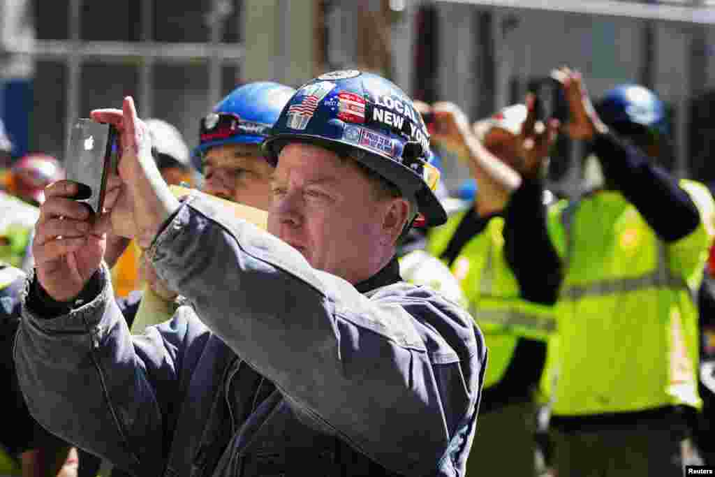Ground Zero workers take photos as the final piece of One World Trade Center's spire is lifted to the top of the building in New York.