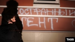 "A woman walks past graffiti saying ""Foreign agents [love the] USA"" on the building used by the Memorial Human Rights Center in Moscow in November 2012."
