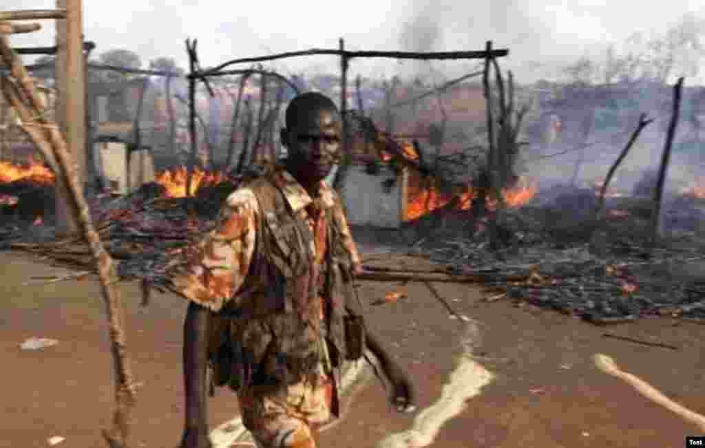 A policeman walks past the smoldering remains of a market in Rubkona near Bentiu in South Sudan on April 23. (AP)