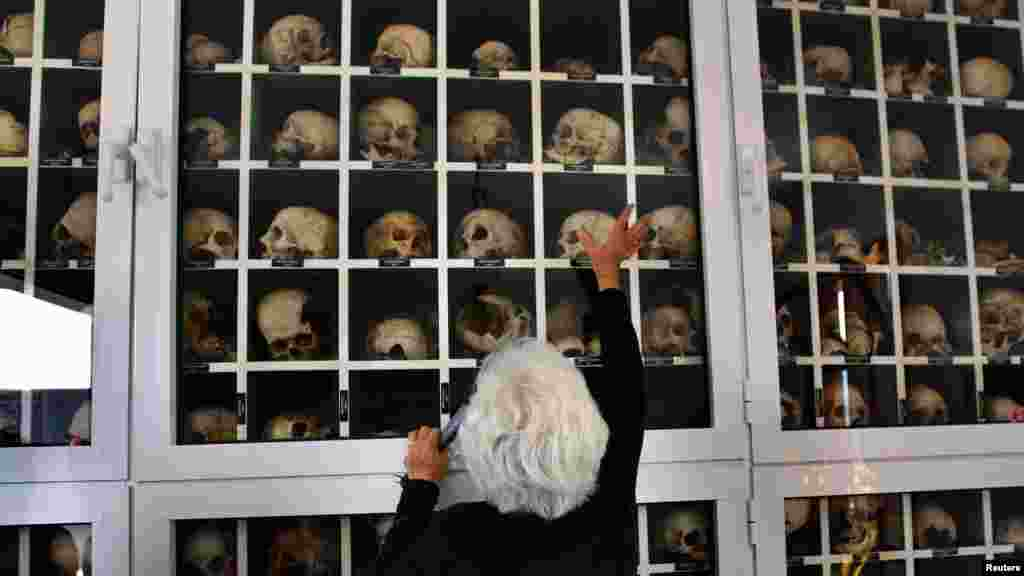 Panayiota Mario, a survivor of the World War II-era Distomo massacre, touches a glass panel containing the remains of victims during the 68th anniversary of that massacre by Nazis in Greece in 1944. (Reuters/Yannis Behrakis)