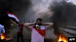 An Egyptian protestor covers his face with his national flag during clashes between supporters of Egypt's ousted President Muhammad Morsi and security forces in Cairo on August 30.
