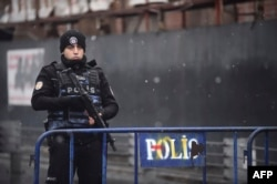 A Turkish police officer stands guard close to the Reina nightclub.