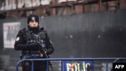 Сотрудник турецкой полиции стоит недалеко от места нападения на ночной клуб в Стамбуле.