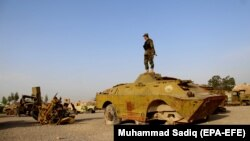 An Afghan soldier stands in a junkyard of Soviet-era tanks in Kandahar in February 2018.