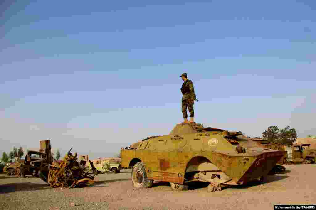 An Afghan soldier stands in a junkyard of Soviet-era tanks on the 29th anniversary of the Soviet-Afghan War, in Kandahar on February 15. (epa-EFE/Muhammad Sadiq)