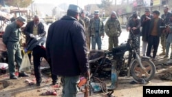 An Afghan police officer stands at the site of a bomb blast in Faryab, March 18, 2014.