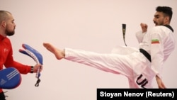 Iranian tae kwon do competitor Farzad Zolghadri practices with Bulgarian national tae kwon do coach Teodor Georgiev during a training session in Sofia on January 30.