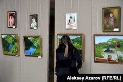 Кәріпбек Күйіков пейзаж салғанды ұнатады. Көрмеге келген қыз суретшінің шығармаларын тамашалап тұр. Алматы, 18 қазан 2019 жыл.