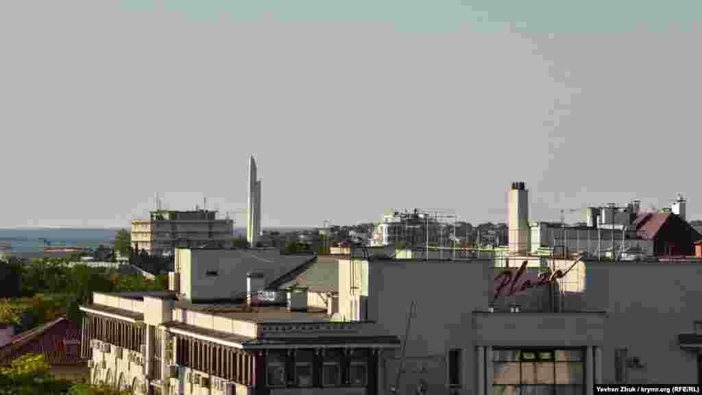 Над дахами будинків вдалині височіє обеліск «Багнет і Вітрило»