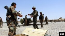 FILE: Members of the Afghan security forces take their positions during an operation against the Taliban in southern Afghanistan.