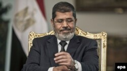 Then-President Muhammad Morsi gestures during an interview with Spanish news agency EFE, in Cairo in May 2013.