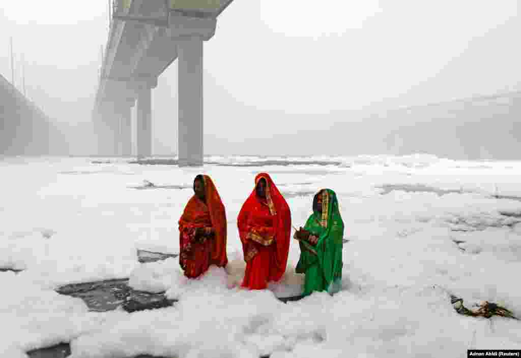 Hindu women worship the sun god in the polluted waters of the River Yamuna during the religious festival of Chatth Puja in New Delhi. (Reuters/Adnan Abidi)