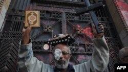 احد مؤيدي حركة 6أبريل يحمل الصليب بيد وبالاخرى القران