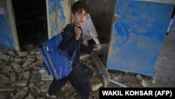FILE: An Afghan schoolboy carries his backpack at a school near the site of a Taliban car bomb attack in Kabul in July.