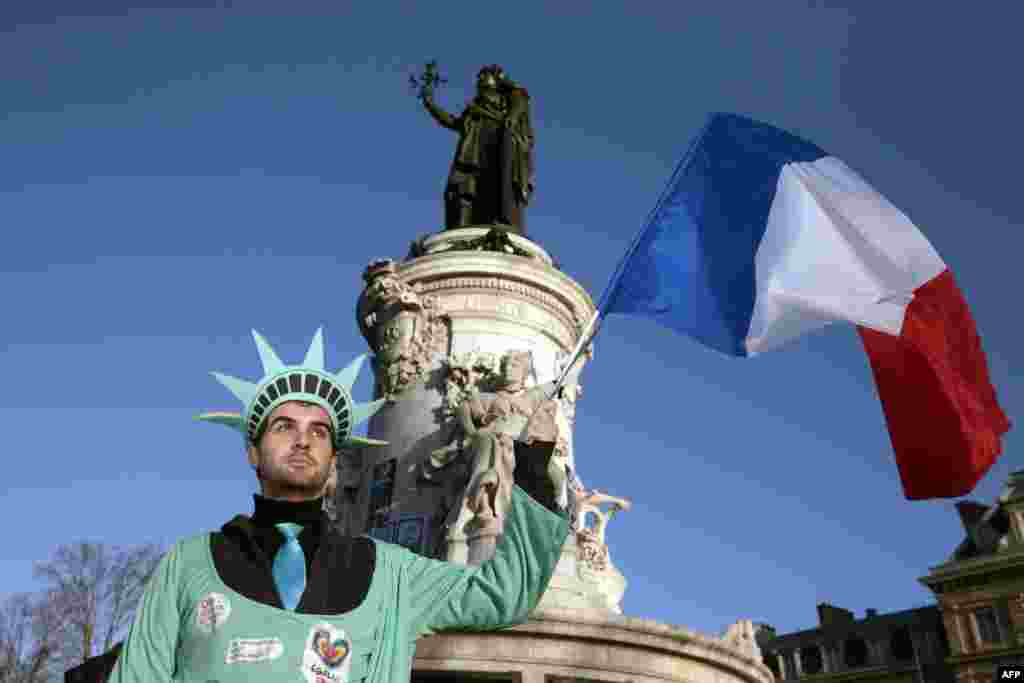 A man, dressed as the Statue of Liberty, holds up the French national flag at the Place de la Republique.
