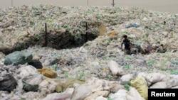 إمرأة عراقية تنبش في النفايات لجمع لقى يمكن الإستفادة منها